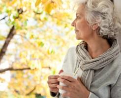 grauhaarige, attraktive Frau genießt den sonnigen Herbst